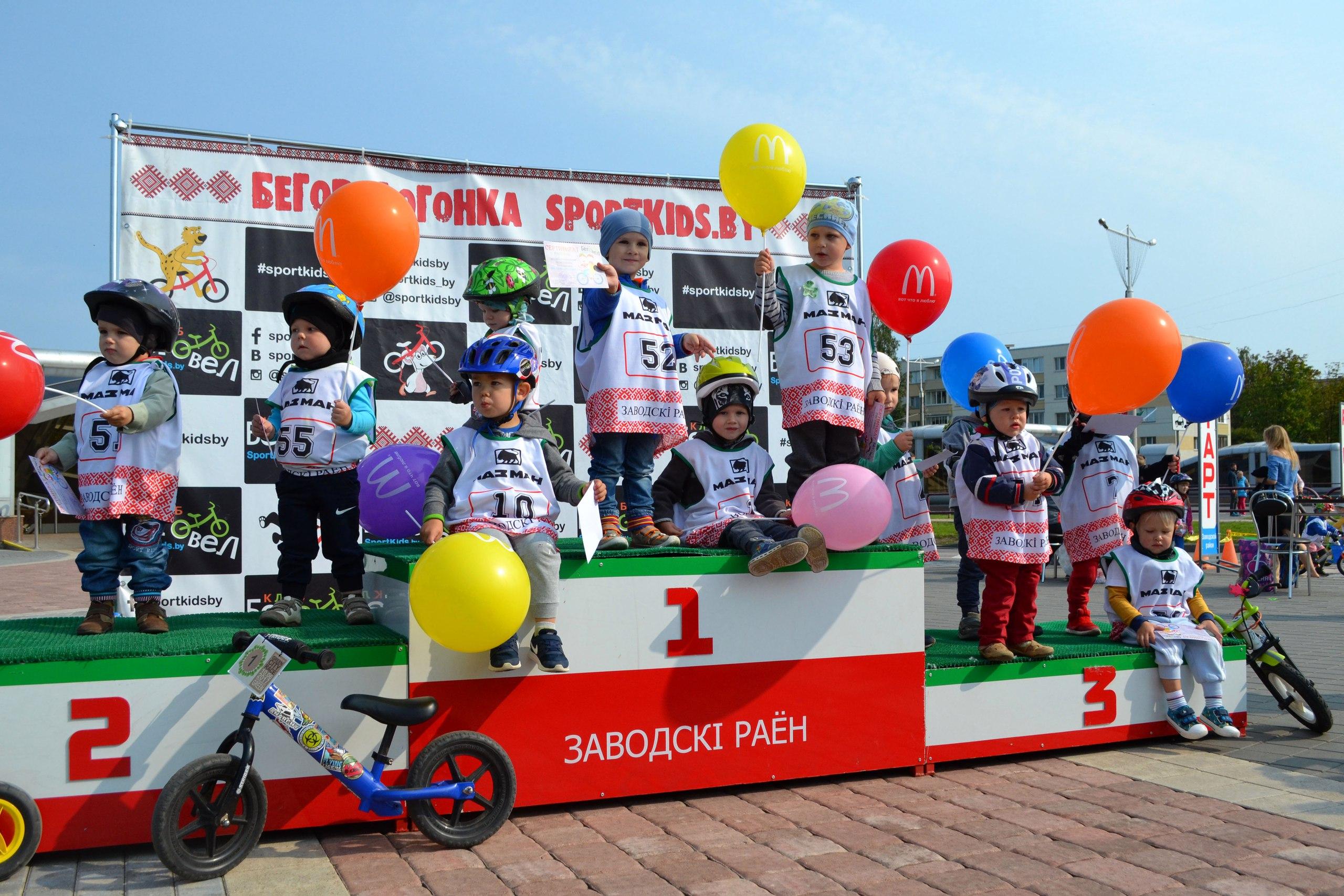 двухлетние малыши-беговелогонщики на пьедестале